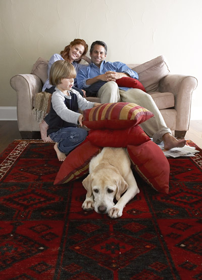 Family relaxing in the den with their dog